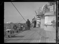 A sailor with a broom and a civilian on the deck of a US Navy battleship
