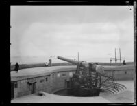 One of the 14-inch caliber guns at Fort MacArthur with the parade of the navy fleet in the background, San Pedro, 1932