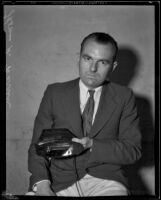 Thomas R. Warren displays his invention, a hand-held ultra-violet lamp, Pomona, 1933