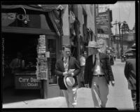 Roy Watkins, of the Angelus Temple, and Everett Davis walk down the street, 1932