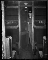 Deputy US Marshal John P. Brooke stands in the door of a railway prison car, Los Angeles, 1935