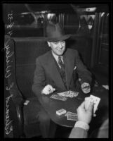 Attorney Edward E. Wiley plays cards on a train on his way to prison, Los Angeles, 1935