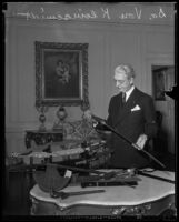 Dr. Rufus B. von Kleinsmid examines swords and other antique weapons, Los Angeles