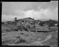 Building debris left by a catastrophic flood and mudslide with an intact-looking house behind it, La Crescenta-Montrose, 1934