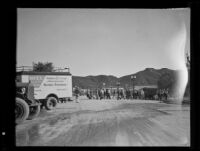 Group of people walking across a street after a catastrophic mudslide, perhaps during relief efforts, Montrose and La Crescenta, 1934