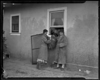 Man in house passes parcel out of window to 2 women after a catastrophic flood and mudslide, La Crescenta-Montrose, 1934