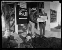 During the post flood and mudslide cleanup effort, two men look at a map, La Crescenta-Montrose, 1934