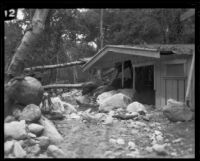 Flood waters rush past a damaged cabin in Little Santa Anita Canyon, Sierra Madre, 1926