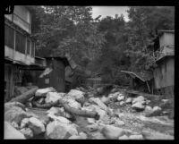 Flood-damaged buildings line a debris-strewn stream in Little Santa Anita Canyon, Sierra Madre, 1926