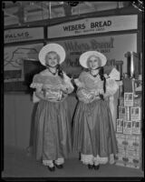 Sylvia and Louise Haines, known as the Weber Gingham Twins, stand in front of the Weber Bread exhibit at the Food and Household Show, Los Angeles, 1933