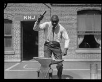 George Godfrey, heavyweight boxer, posing with anvil [outside the KJH Radio studio, Los Angeles(?)], circa 1926-1927