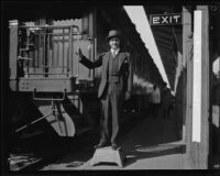 Harry Frank Guggenheim poses next to train