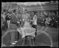 Golfer Walter Hagen, Max Turner and Helen Robinson cutting cake at the 4th annual Pasadena Open tournament, Pasadena, 1931-1932