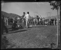 Walter Hagen waits and watches another golfer tee-off