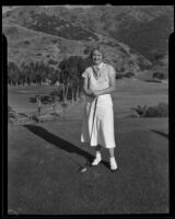 Golfer Mrs. Harry Hall poses with her club on the course, 1926-1939