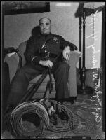Sheriff Deputy John W. Hanby in a living room with firearms and gear, Los Angeles, 1935