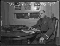 Sheriff Deputy John W. Hanby at a kitchen table with firearms, Los Angeles, 1935
