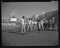 Coach Howard Jones instructing his team at the Coliseum. Los Angeles, 1925-1939