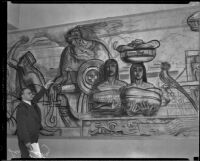 At a mural exhibition at the Los Angeles Central Library, artist Leo Katz points to an area of a cartoon drawing for the Frank Wiggins Trade School mural, Los Angeles, 1934