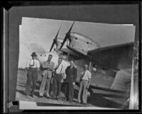 Australian aviator Sir Charles Kingsford-Smith with 4 unidentified men at an air field, 1927-1935