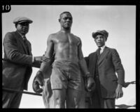 Sam Langford, boxer, in the corner of a ring between 2 staff members