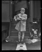 Child actor Jackie Kelk and his kitten arrive by train to Los Angeles, Los Angeles, 1933