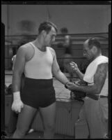 Jerry the Greek laces up the boxing gloves of Kingfish Levinsky, Los Angeles, 1934