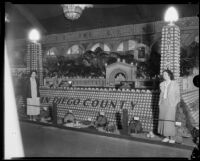 Two women stand in front of the San Diego County display at the Los Angeles County Fair, Pomona, 1933