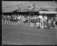 Man prepares a child to race go-karts at the Los Angeles County Fair, Pomona, 1933