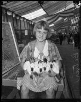 Betty Betzer holds four rabbits at the Los Angeles County Fair, Pomona, 1933