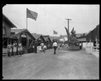 Visitors to the Los Angeles County Fair stroll along a midway lined by livestock stables, Pomona, 1930