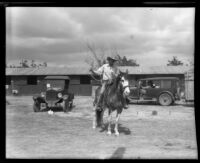 Horse and rider pose outside the stables at the Los Angeles County Fair, Pomona, 1930