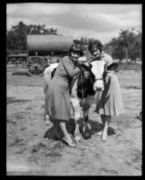 Two young women pose with a cattle at the Los Angeles County Fair, Pomona, 1930