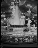 Helen Cox, 1933 queen of the LA County Fair, and Ann Harriet Pettus, 1934 queen of the LA County Fair, posing next to the Los Angeles exhibit, Pomona, 1934