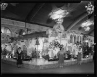 Three women stand in front of the Yorba Linda display at the Los Angeles County Fair, Pomona, 1932