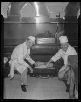 Cooks in the Los Angeles County General Hospital kitchen place a pan of meats into an oven, Los Angeles, [1934]