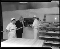 Cooks in the Los Angeles County General Hospital kitchen remove a pan from the oven, Los Angeles, [1934]