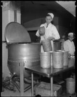 Cook in the Los Angeles County General Hospital kitchen stands beside a vat and pours liquid into a pot, Los Angeles, [1934]