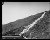 Water rushes down the hillside along a dynamited section of the Los Angeles Aqueduct in No-Name Canyon, Inyo County vicinity, [circa 1927]