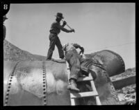 Workers make repairs on a damaged section of the Los Angeles Aqueduct in No-Name Canyon, Inyo County vicinity, [about 1927]