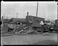 Resident of Hooverville chops wood for fire, Los Angeles, 1930s