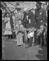 "Councilman Baker and a police officer stand beside Milton ""Buddy"" Coleman as he cuts the ribbon to dedicate the Sixth Street Viaduct, Los Angeles, 1933"