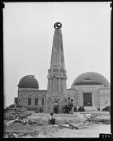 Astronomers Monument at the nearly completed Griffith Observatory, with 3 girls writing on the base with chalk, Los Angeles, circa 1934-1935