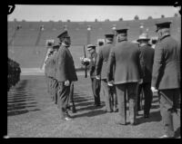 Chief Davis handles a firearm during the annual police inspection at Los Angeles Memorial Coliseum, Los Angeles, 1927