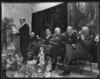 Gordon L. McDonough, Harry M. Baine, Earl E. Jensen, and Hugh A. Thatcher observe from their seats as Dr. Percy T. Magan speaks at the podium, Los Angeles, 1934