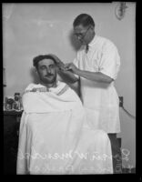 A barber named Parkers gives Loren W. Mendell a haircut, Los Angeles, 1929