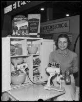 Woman demonstrates electric can opener at National Housing Exposition, Los Angeles, 1935