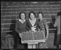 Three women hold a box of lemons at the National Orange Show, San Bernardino, 1931