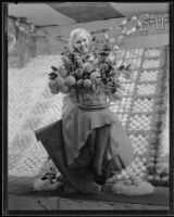 Pat Graham holds a basket of oranges at the National Orange Show, San Bernardino, 1933