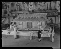 Two women stand in front of the Corona display at the National Orange Show, San Bernardino, 1933